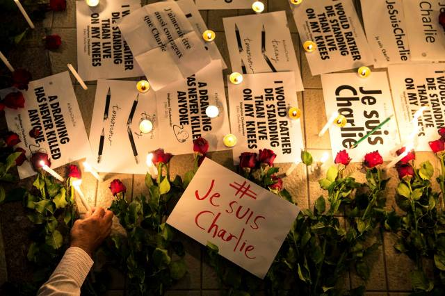 A man places a candle next to messages and flowers during a vigil at the Bangkok Art and Culture Centre to pay tribute to the victims of a shooting by gunmen at the offices of weekly satirical newspaper Charlie Hebdo in Paris