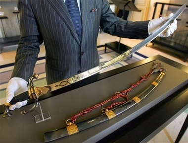 ** FILE ** French auctioneer Jean-Pierre Osenat presents a gold-encrusted sword Napoleon wore into battle in Italy in June 1800, in this May 25, 2007 file photo taken in Paris. The last of Napoleon's swords in private hands, it has an estimated value of euro1.2 million to euro1.5 million (USD1.6 million to USD2 million). The Osenat auction house, managing the sale, said it may sell for two to three times that amount. It will be auctioned off Sunday, June 10, 2007 across the street from one of Napoleon's imperial castles in Fontainebleau, south of Paris. (AP Photo/Remy de la Mauviniere, file)