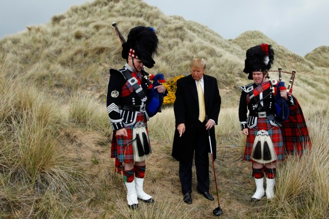 U.S. property mogul Donald Trump (C) poses next to bagpipers during a media event on the sand dunes of the Menie estate, the site for Trump's proposed golf resort, near Aberdeen, north east Scotland May 27, 2010. REUTERS/David Moir (BRITAIN POLITICS - Tags: SPORT GOLF BUSINESS) - RTR2EF9L