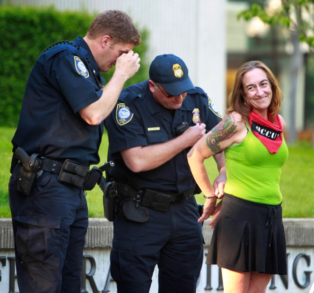 FILE-This July 10, 2012, file photo shows Occupy Eugene member Emily Semple, right, smiling as she is placed under arrest by Federal Police after she refused to leave the outdoor plaza at the Federal Courthouse in Eugene, Ore. (AP Photo/The Register-Guard, Chris Pietsch, File)